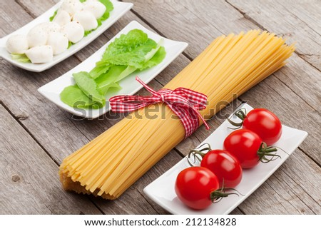 Tomatoes, mozzarella, pasta and green salad leaves on wooden table background