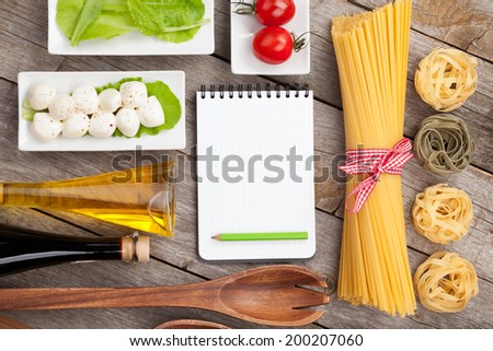 Tomatoes, mozzarella, pasta and green salad leaves on wooden table background with notepad for copy space - stock photo