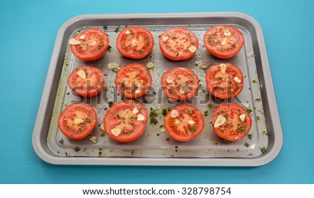 Tomatoes on a baking tray, seasoned with thyme and garlic, drizzled with olive oil for roasting - stock photo
