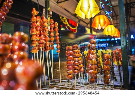 Tomatoes on sticks in winter, traditional Chinese snacks. Located near Modern Hotel Harbin of Central Avenue (Zhongyang Street), Harbin City, Heilongjiang Province, China. - stock photo