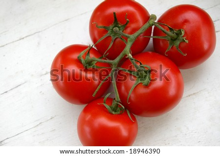 Tomatoes on the vine against weathered white background - stock photo