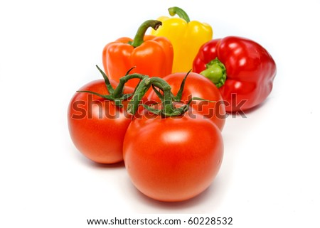 Tomatoes on the vine and bell peppers in the background