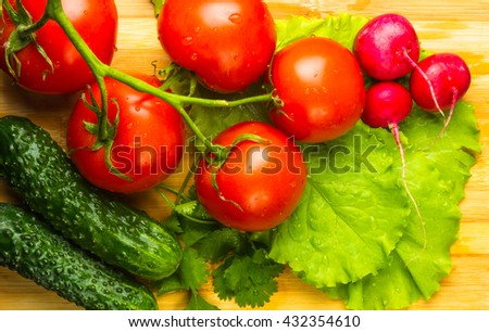 Tomatoes on twig, cucumbers, lettuce and cilantro on a wooden Board