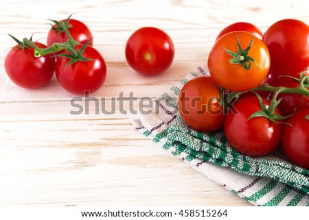 Tomatoes on vine on white rustic wooden background
