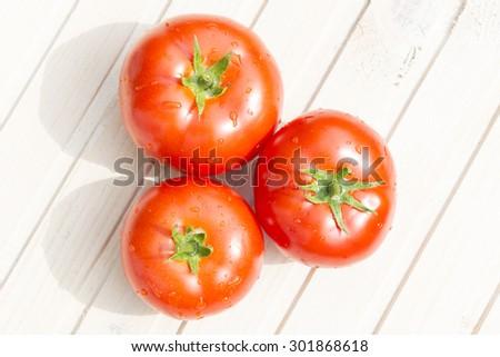 Tomatoes on wooden background on sunlight - stock photo