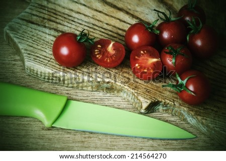 tomatoes on wooden mat with knife