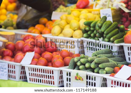 Tomatoes, oranges, lemons, cucumbers? grapes and pumpkin in boxes on city market - stock photo