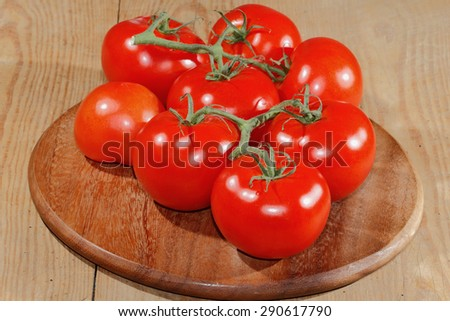 Tomatoes panicles on a wooden chopping board - stock photo
