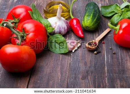 Tomatoes, paprika, basil and garlic on wooden table, ingredients for gazpacho - stock photo