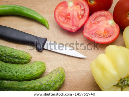 Tomatoes, pepper, cucumbers and a knife on a wood board - stock photo