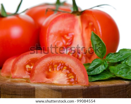Tomatoes presentation sliced on wooden plank macro view isolated on white background