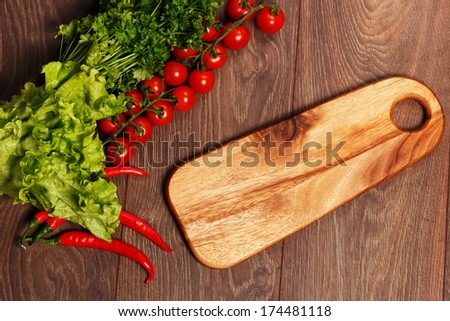 Tomatoes, salad and parsley with a cutting board - stock photo