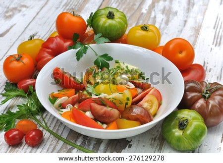 tomatoes salad in plate withe different variety  on wooden table - stock photo