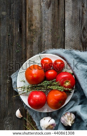 Tomatoes, thyme, garlic on textured rustic wooden background. Fresh natural cooking ingredients and copy space for text.  - stock photo