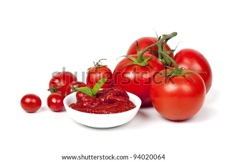 Tomatoes with a dish of tomato paste garnished with basil, over white background. - stock photo