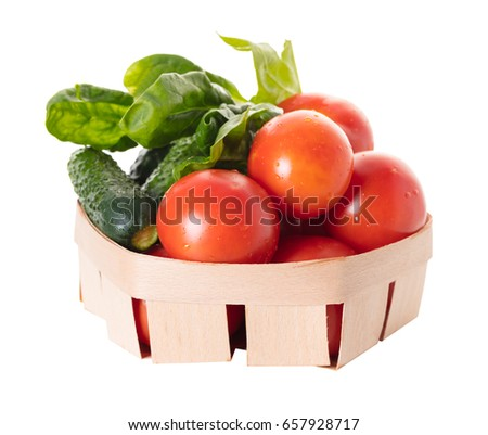 Tomatoes with cucumber and spinach leaves in a basket on white isolated background