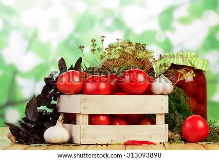Tomatoes with garlic in wooden cart on table for canning - stock photo