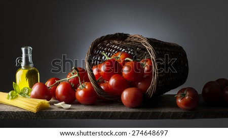 Tomatoes with spaghetti basil and olive oil on the wooden table