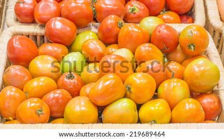 tomatos harvested products on wooden basket.