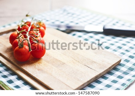 tomatos on cutting board with knife