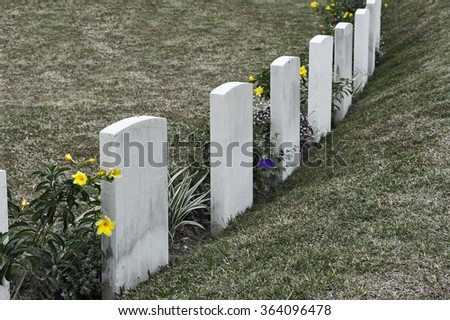 Tombstone and graves in an ancient church graveyard - stock photo