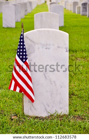 tombstone on a national cemetery with the american flag - stock photo