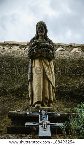 Tombstone with the Christ holding the lamb statue and the crucifix at beneath. Old cemetery in Les Baux-de-Provence (Provence, France). - stock photo