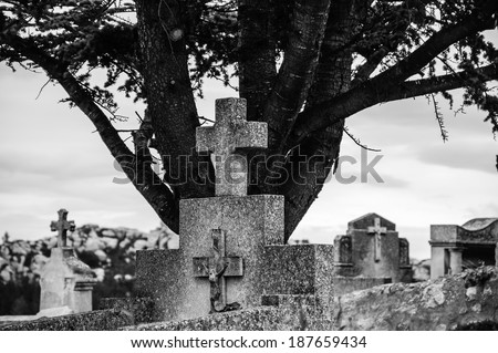 Tombstone with the cross and crucifix at the old cemetery in Les Baux-de-Provence (Provence, France). Aged photo. Black and white. - stock photo