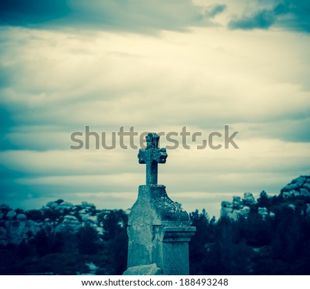 Tombstone with the cross at the old cemetery in Les Baux-de-Provence (Provence, France). Aged photo.  - stock photo