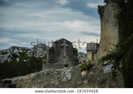 Tombstone with the crucifix behind the old cemetery wall in Les Baux-de-Provence (Provence, France).  - stock photo