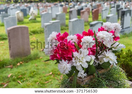 Tombstones on a graveyard in Fall with flowers in the foreground - stock photo