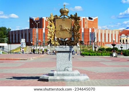TOMSK, RUSSIA - AUGUST 3, 2008: Tomsk Coat of Arms Monument on the background of Tomsk Regional State Philharmonic. The monument was unveiled in 2004 to commemorate the 400th anniversary of the city. - stock photo