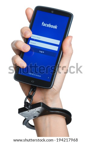 TOMSK, RUSSIA - MAY 22, 2014: Hand chained with smartphone where Facebook application started. According to wikipedia some users become addicted to the social networking sites such as Facebook. - stock photo