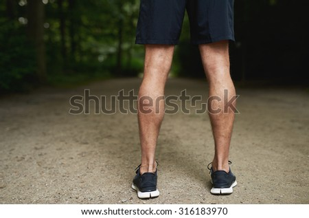 Tone Calf Muscle of a Fit Young Guy Standing at the Park and Facing Backwards. - stock photo