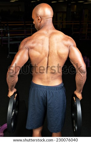 Toned and ripped lean muscle fitness man holding plate weights. - stock photo