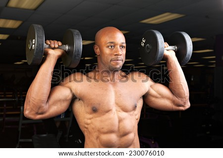 Toned and ripped lean muscle fitness man lifting weights. - stock photo