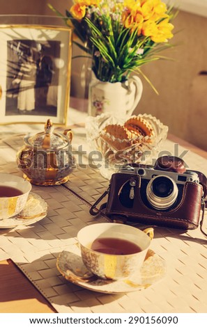 Toned background with Cup of  tea, summer flowers, old foto and vintage camera - stock photo