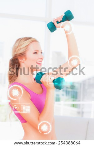 Toned blonde lifting dumbbells and smiling against fitness interface