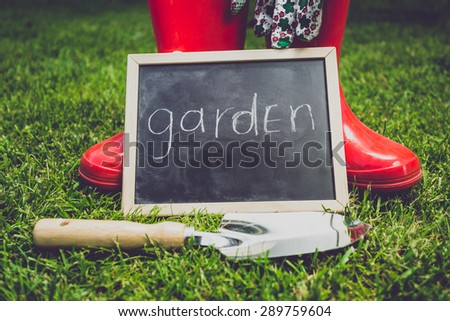 "Toned closeup photo of blackboard with word ""Garden"" lying on grass next to garden tools - stock photo"
