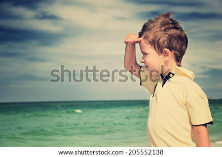 toned image boy looking away from his palm on the background of cloudy sky and sea. horizontal - stock photo