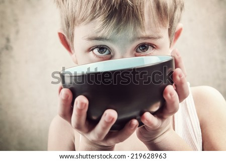 Toned image of a hungry child holding an empty bowl.