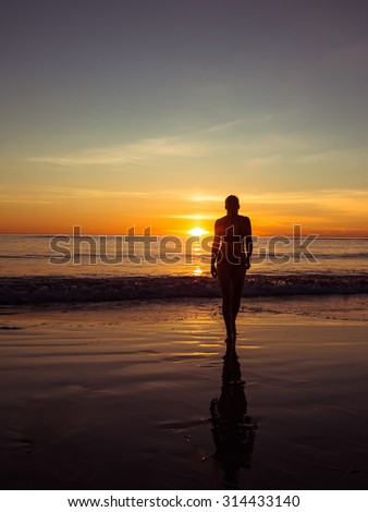 Toned image of a silhouette of an adult woman walking on the beach at sunset and colored background of the waves - stock photo