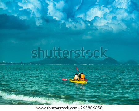Toned image of a yellow kayak with two tourists sails on the sea on the background of dramatic sky with cumulus clouds
