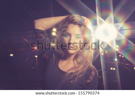 toned image of beautiful 20s girl touch hair by hand on night city background with big stars of loght - magical look