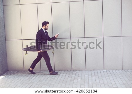 Toned image of confident businessman walking with longboard and using mobile or smart phone on way to his office.