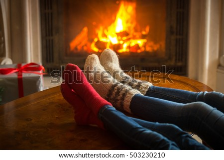 Toned image of couple wearing woolen socks relaxing by the fireplace at house