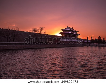 Toned image of the fortress with a tower Forbidden City in Beijing on the background of sunset at clear sky and colorful reflections in the water