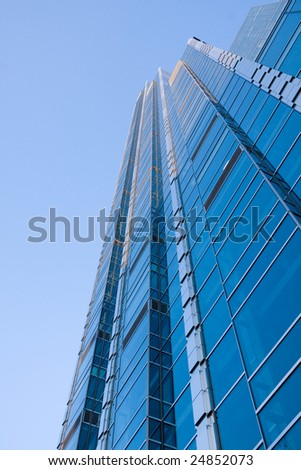 Toned image of very high office building made of glass and steel. Copy space left.