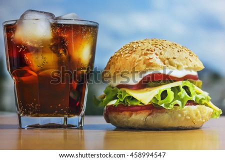 Toned image, square picture. Closeup of a glass of cola and burger on the background of the modern city. Concept: fast food. Top view, closeup.