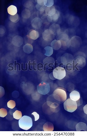 Toned in blue bokeh lights on black background, drops of water flying in the air defocused - stock photo
